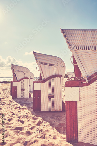 Foto Spatwand Strand Vintage toned picture of wicker hooded basket chairs on a beach at sunset, summer holidays concept.