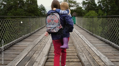 Wall mural Mother and child girl daughter walking the pedestrian bridge together