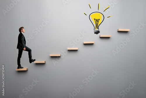 businessman climbing steps towards light bulb buy photos ap