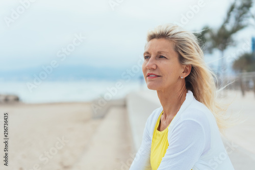 Leinwanddruck Bild Thoughtful older woman on a seafront promenade
