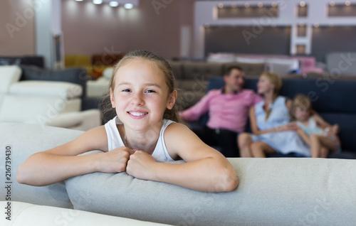 Foto Murales Postrait of cute child girl is standing near new sofa
