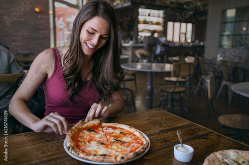 Zobacz obraz Smiling woman at hip artisanal pizzeria grabbing a slice of delicious craft pizza