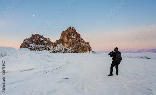 Foto Murales Travelling in winter, photographer carrying camera tripod at frozen lake Baikal in Siberia, Russia