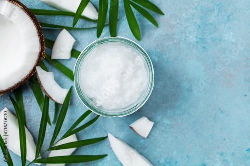 Fototapeta samoprzylepna Organic coconut oil in jar and coconut fruit top view. Spa cosmetic and food ingredient. Flat lay.