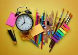 Alarm Clock and School Stationary on Yellow Background