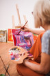 Elderly woman is painting in her home. Retirement hobby. - 216781083