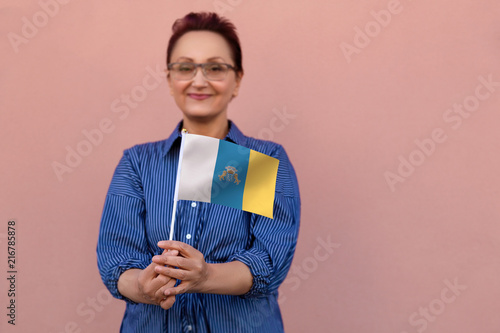 Fotobehang Canarische Eilanden Woman holding Canary Islands flag. Nice portrait of middle aged lady 40 50 years old with autonomous Canary Islands Spain flag. Visit Canary Islands concept.