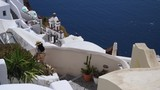 A beautiful woman in a long dress walks down the white stone steps of Santorini, Greece while visiting on vacation - 216792484