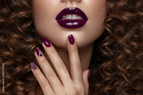Leinwanddruck Bild Beautiful girl with evening make-up, purple lips, curls and design manicure nails. beauty face. Photos shot in studio.