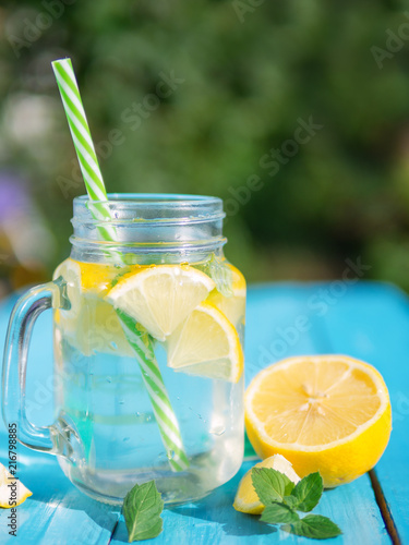 Canvas Sap Lemonade in a glass jar with slices of lemon and mint on a wooden table