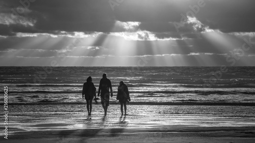 Black And White Photo Of Three People Walking At The Piha Beach West Auckland