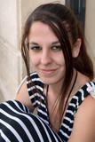 Portrait en extérieur d'une jeune femme brune aux cheveux longs - 216803203
