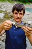 teen ager fisherman shows happy, catching an Salvelinus alpinus in an alpine lake