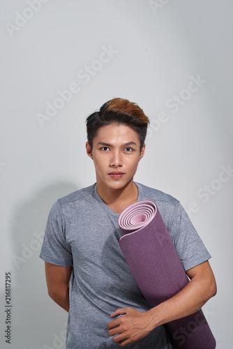 Obraz na płótnie Attractive asian man with yoga mat posing in a studio