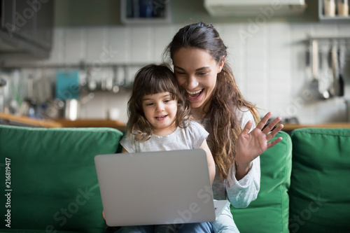 Happy mother and kid daughter waving hands looking at web camera using laptop for video call, smiling mom and child girl having fun greeting online by computer webcam making videocall via application - 216819417