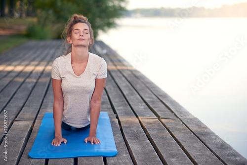 Foto Spatwand School de yoga Junge Frau macht eine Yoga Übung am See