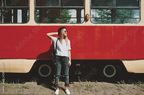 Leinwandbild Motiv Carefree hipster girl posing with tram in background