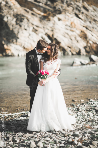 Elegant stylish happy brunette bride and gorgeous groom on the background of a beautiful river in the mountains - 216828462