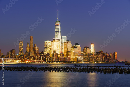 Lower Manhattan skycrapers illuminated at twilight with the Hudson River. Manhattan, New York City