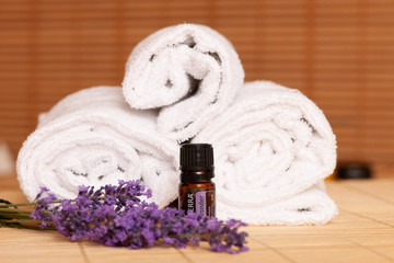 White towels and massage rocks in spa salon over dark and light bamboo background © Samo Trebizan