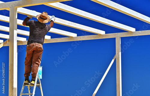Foto Murales Man putting a wooden structure on the beach