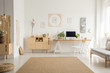 Leinwandbild Motiv Brown carpet between pouf and grey sofa in white home office interior with chair at desk. Real photo