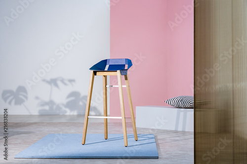 Foto Murales Real photo of an art gallery interior with a blue bar stool with wooden legs on display against pastel pink wall