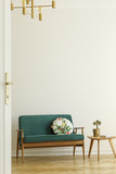 Floral pattern pillow on a retro style, green sofa and a wooden table in a minimalist living room interior with white wall and herringbone floor. Real photo.