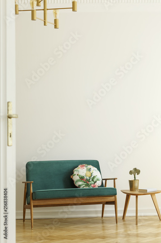 Floral pattern pillow on a retro style, green sofa and a wooden table in a minimalist living room interior with white wall and herringbone floor. Real photo. - 216838404