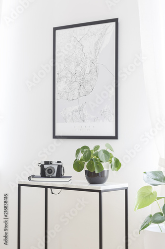 Fototapeta A city map poster on a white wall, plant and camera on a box frame, marble top table in a stylish living room interior for a traveler