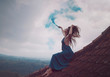 Beautiful woman in long dress sitting with blue colored smoke on tiled red roof of the house against amazing mountain view and cloudy sky background