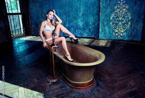 Leinwandbild Motiv beautiful young woman   sitting on a bathtoob