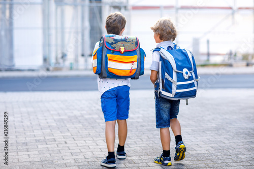 Leinwandbild Motiv Two little kid boys with backpack or satchel. Schoolkids on the way to school. Healthy adorable children, brothers and best friends outdoors on the street leaving home. Back to school. Happy siblings.