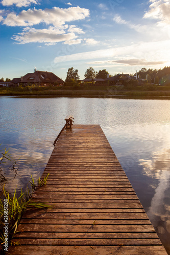 Aluminium Pier Beautiful wooden pier with clouds and sun reflected on calm and blue water