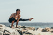 sporty shirtless man doing arm balance on rocky seashore