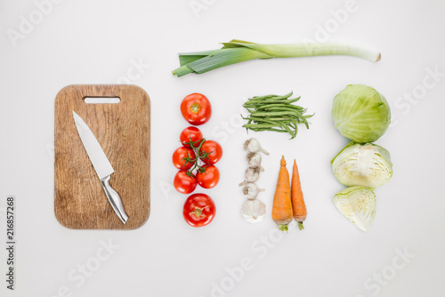 Leinwanddruck Bild top view of ripe vegetables and cutting board with knife isolated on white