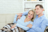 Couple at home on the couch talking and smiling - 216862046