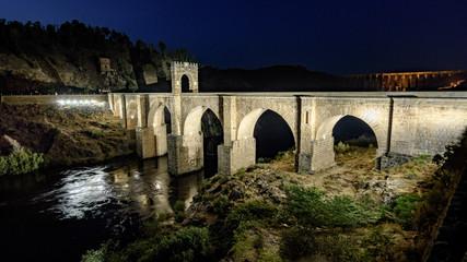 Night panorama of Alcantara (Caceres, Spain) and its Roman bridge over the river Tajo