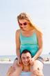 Quadro Man giving girlfriend piggyback ride on marina