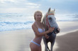 Sexy young woman walking with horse at the beach, horseback
