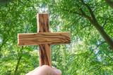 Hand hält ein Holzkreuz im Wald
