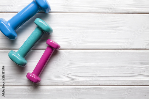Foto Murales Colorful dumbbells on a wooden background
