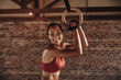 Fit woman holding gymnast rings at the gym