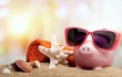 Leinwandbild Motiv Piggy bank on sandy beach background