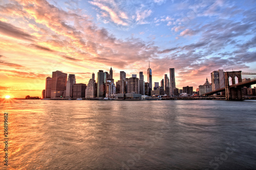 Leinwanddruck Bild New York City Lower Manhattan with Brooklyn Bridge at Sunset