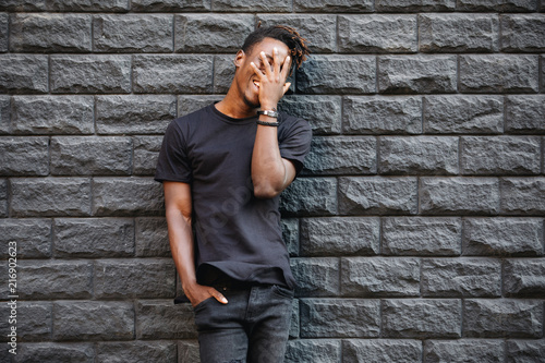 Foto Murales African american man in black t-shirt laughing against brick wall, palm on face