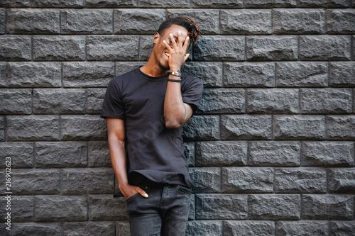Amerykanin afrykańskiego pochodzenia mężczyzna śmia się przeciw ściana z cegieł w czarnej koszulce, palma na twarzy