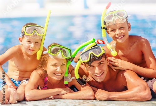 Happy family playing in swimming pool - 216908835
