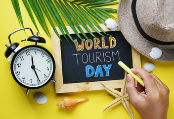 World Tourism Day Typography. Hand Holding Yellow Chalk and Blackboard