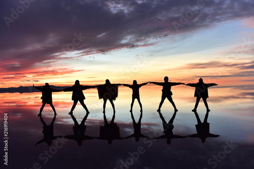 Foto Spatwand Strand Group of people dancing playing with sunset beach lake nature